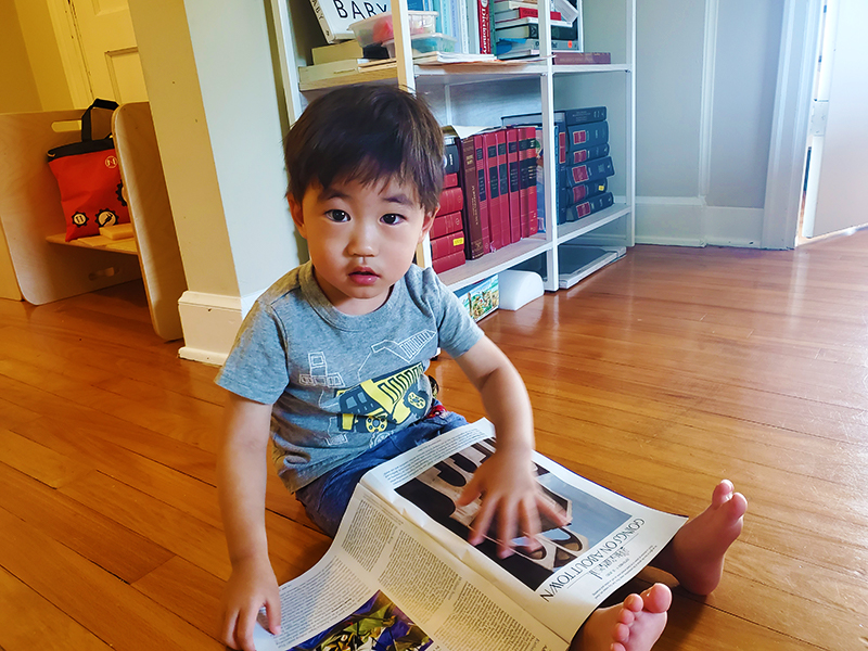 Ray reads a magazine on the floor.