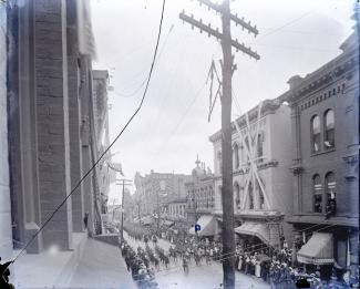 Parade coming down 5th Ave between Church and Union, in 1897