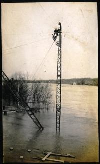 Photo of a recent flood, early 20th century, with two men sitting on top of a crane to escape the water