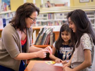 woman helping two young library visitors