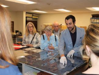 group of people looking at an archival document